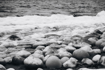 ice stones on the river bank black and white photo
