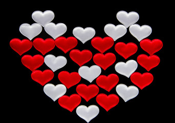 A lot of red and white hearts on a black background in the form of a heart