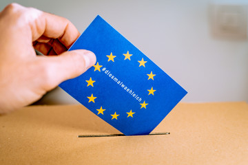 Election in European Union - voting at the ballot box. Hand putting in the ballot box an EU flag vote with thistimeimvoting in german, diesmalwaehleich, hashtag campaign