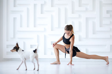 Woman doing yoga In studio and her dog next to her.