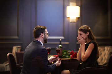 Surprised girl hiding her face in hands while young man making proposal to her in restaurant on valentine day