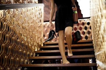Drunk young woman in black dress holding her shoes, handbag and bottle of wine while walking downstairs inside restaurant
