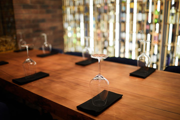 Wooden table in restaurant served with several wineglasses standing upside down on folded black napkins