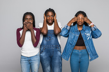 Three young african woman in casual clothes showing blind, deaf and dumb: wise monkey scene - hear no evil, see no evil, speak no evil isolated at white background