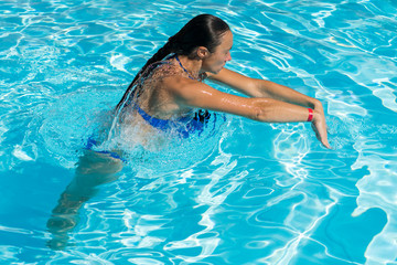 Woman diving in the swimming pool. Young beautiful girl swimming in pool. Brunette relaxing in clear warm water on sunny day. Top view Close up Slow motion.
