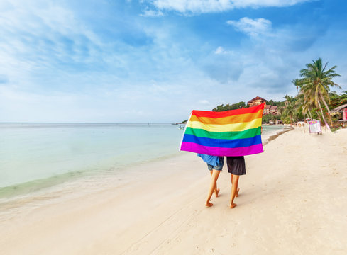 Young lesbian couple walks on a bright tropical beach with a rainbow flag, equal rights, symbol of lgbt community