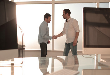 business background.modern office and a handshake of business partners