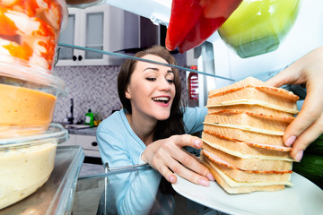 Woman Taking Sandwich From Refrigerator