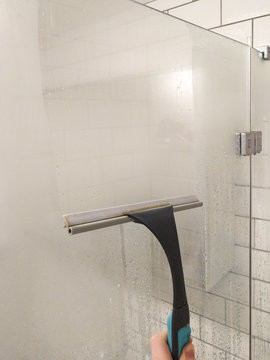 Cleaning concept - hand cleaning glass window pane in bathroom with shower wiper. Shower squeegee.