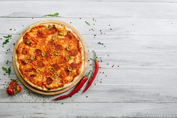 Pizza Pepperoni with mozzarella, salami, pepper and olives on the white wooden background