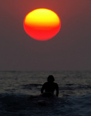 An Balinese surfer heading toward sunset in Kuta.