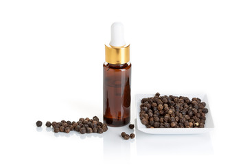 Black pepper essential oil isolated on white background. Black pepper oil bottle with dropper for beauty, skin care, wellness and medicinal purposes. Piper nigrum oil