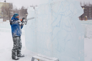 The sculptor cuts a figure from an ice block with a gasoline saw