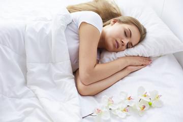 Beautiful girl sleeps in the bedroom, lying on bed