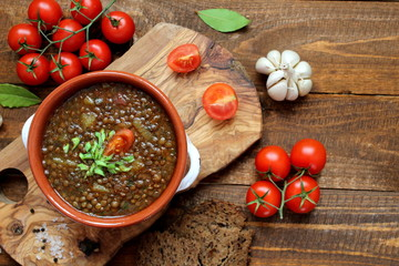 Delicious lentils soup on wooden background. Top view with copy space. Diet food. Vegetarian and vegan food.
