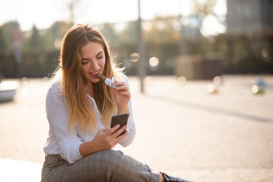 Teenage woman outside chatting on phone, having energy bar.