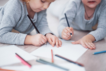 Children lie on the floor in pajamas and draw with pencils. Cute child painting by pencils. Hand of child girl and boy draw and paint with crayon. Close up view
