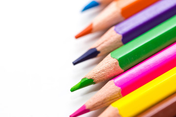 Color pencils in a row close up macro shot on white background, space for text.