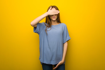 Young redhead girl over yellow wall background covering eyes by hands. Do not want to see something