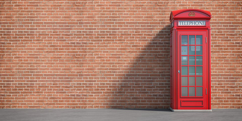 Red phone booth on brick wall background. London, british and english symbol. Space for text