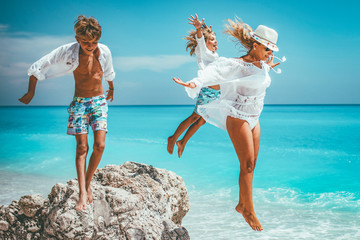 Happy young mother with her little kids having fun at the sunny beach. They are jumping from the rock.