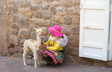 Peruvian little girl in traditional dress with baby llama on the street of Cusco, Peru, Latin America. Horizontal close up. Selective focus
