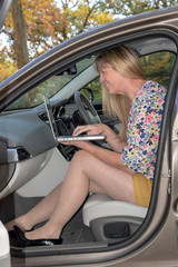 Woman seated in a car using a laptop computer