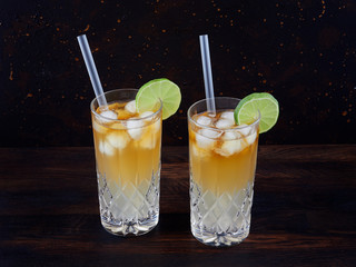 Dark 'n' stormy, a cocktail made using dark rum, ginger ale or beer, served in a highball glass filled with ice and garnished with a slice of lime
