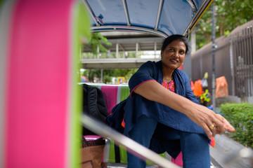 Mature beautiful Indian woman sitting in tuk tuk