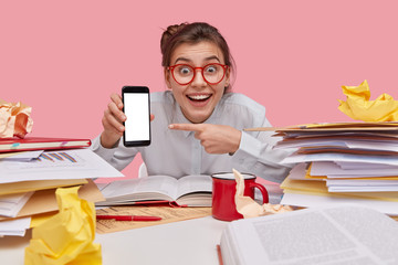 Satisfied schoolgirl with happy expression, toothy smile, points at mobile phone with empty screen for your promotional content, surfes internet, studies economical issues, isolated on pink wall