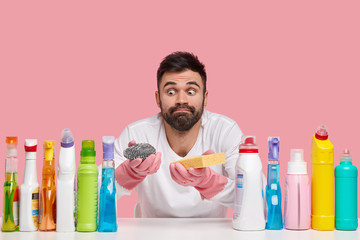 Indoor shot of surprised bearded man looks with eyes popped out, wears casual clothes, uses different detergents, isolated over pink background, prepares for washing dish. Apartment cleaning