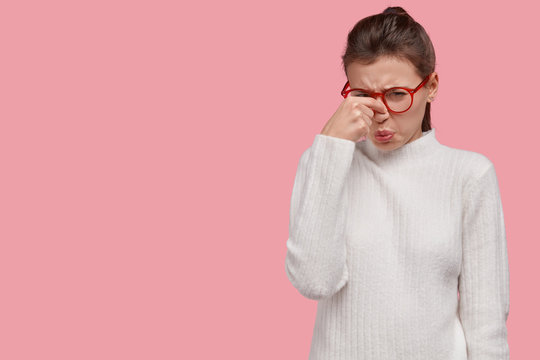 Upset young European woman covers nose with hand, smells stink, expresses dislike, wears spectacles and white clothes, models over pink background with free space for your promotional content