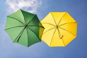 Grüner und gelber Regenschirm im Himmel