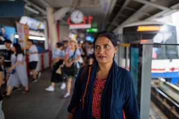 Mature beautiful Indian woman at train station thinking