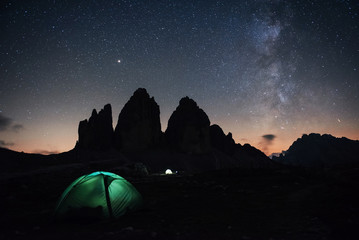 Our galaxy is on the sky. Two lighting tents with tourists inside near the Tre Cime three peaks mountains at night time