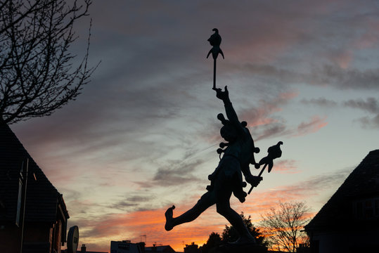 silhouette of court jester or imp toy dancing over rooftops