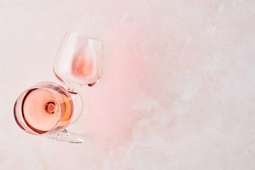 Summer drink. Glass of rose wine on pink background with copy space for text. Top view. Horizontal.