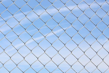 A close up photograph of a section of wire fencing, against a blue sky.  Security, safety concept. Barrier