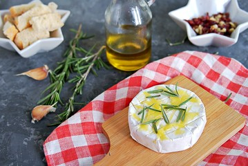 Camembert or brie cheese, prepared for roasting with garlic, rosemary and olive oil on a dark gray background.