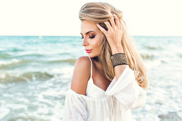 Close-up portrait of blonde girl with long hair dreaming on sea background. She wears white clothes and ornamentation on hand. She looks down.