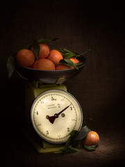 Oranges, tangerines on scales on rustic hessian. Dark, chiaroscuro style still life. Vintage theme. Vertical shot.