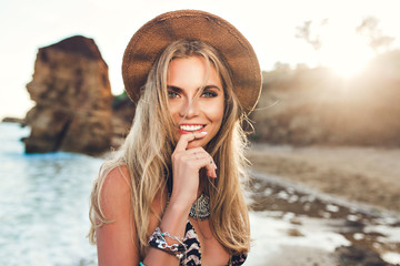 Closeup portrait of attractive blonde girl with long hair posing on rocky beach on sunset background. She wears bikini, hat. She holds finger on lips and smiles to the camera.