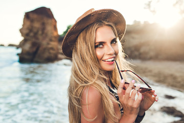 Closeup portrait of attractive blonde girl with long hair posing on rocky beach. She wears bikini, hat. She holds sunglasses and smiles to the camera.