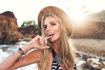 Portrait of attractive blonde girl with long hair posing on rocky beach on sunset background. She wears bikini, hat. She holds finger on lips and looks to the camera. Wall mural