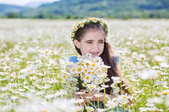 Cute little smiling girl in the chamomile field
