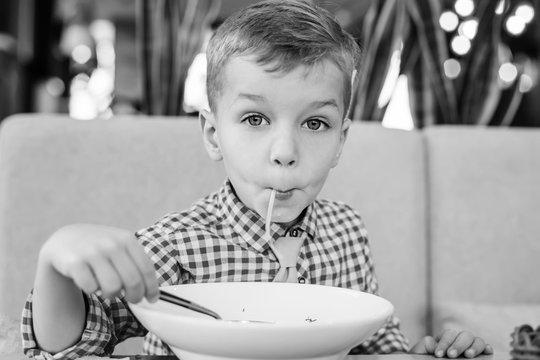 Funny little boy eating noodle soup