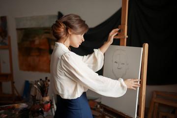 Cute female artist drawing in studio