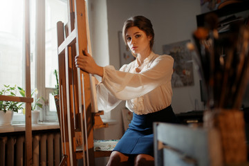 Female artist works at the easel in studio
