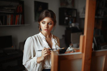 Thoughtful female painter with color palette