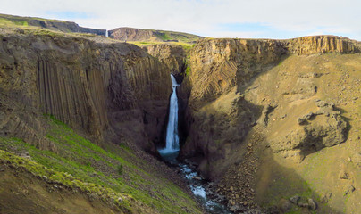 Magnificent Litlanesfoss waterfall, also called Stuðlabergsfoss, surrounded by long basalt columns, along the way to famous Hengifoss, Iceland